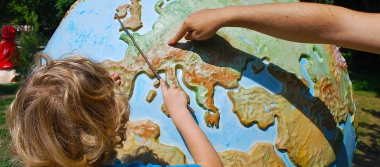 Child with globe and pointer